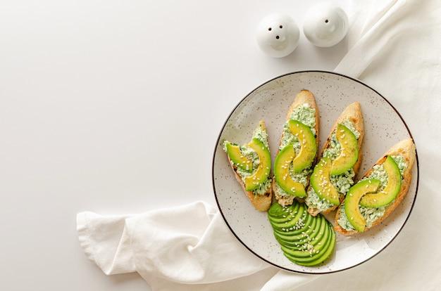 Открытые бутерброды из свежего французского багета, рикотты и шпината на белом столе. концепция завтрака. вид сверху, копия пространства