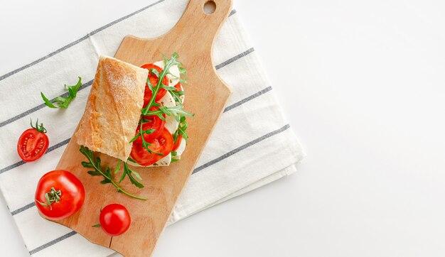 Сэндвич с моцареллой на деревянной разделочной доске. итальянская закуска концепции. вид сверху, накладные расходы. копировать пространство