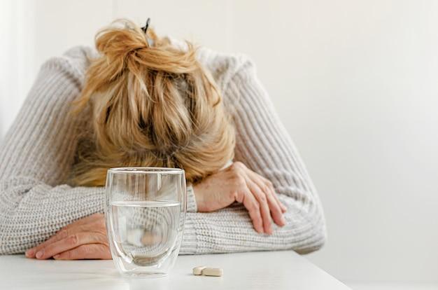 Пожилая женщина чувствует себя подчеркнуто. селективный акцент на стекло и таблетки. концепция лечения депрессии