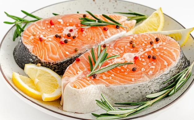 コショウ、海塩、ローズマリー、白レモンのサーモンまたはマスステーキ。トップビュー、ケトダイエット、健康的な食事のコンセプト。