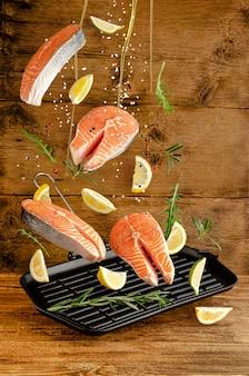 スパイスとハーブの木製の背景にグリル鍋に落ちる新鮮なサーモンやマス魚。空飛ぶ食べ物と空中浮揚の概念。