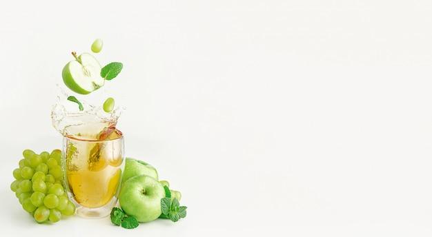 Яблоко, виноград и мята летят над стаканом брызг свежего сока. биологическая пища и концепция здорового образа жизни.