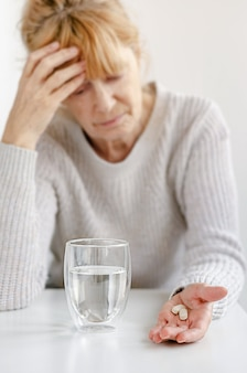高齢者の女性が彼女の頭に手を握っています。錠剤とコップ一杯の水の選択的な焦点。頭痛とストレスの概念