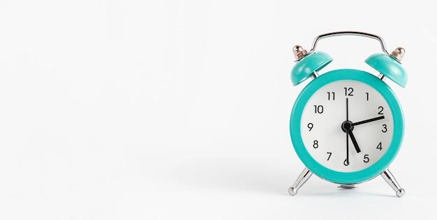 白い壁にターコイズブルーの目覚まし時計。バナー、コピースペース。