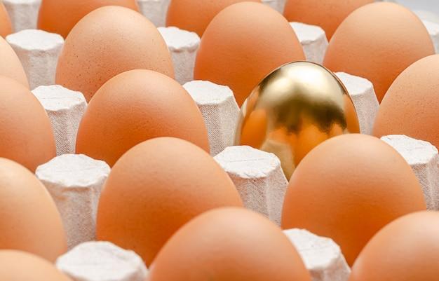 Золотое яйцо в ряд. из коробки мышления концепция.