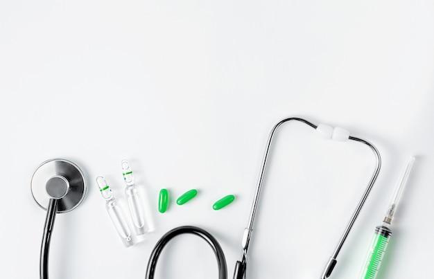 聴診器、アンプル、錠剤、白い壁に注射器。平置き、オーバーヘッド。コピースペース