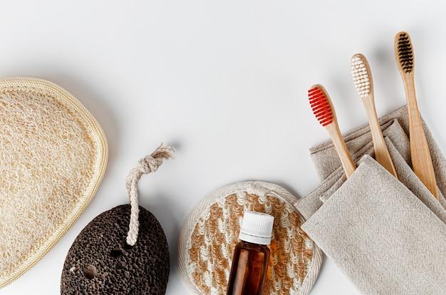 竹の歯ブラシ、顔と体のスポンジ、エッセンシャルオイルと軽石。コピースペース。廃棄物ゼロの浴室付属品