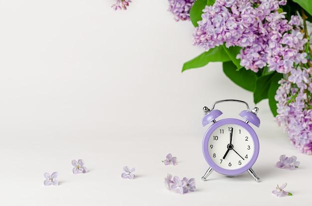 ライラック色の花と目覚まし時計の朝の背景。