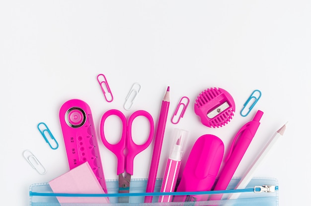 Розовые школьные принадлежности на белом фоне. копирование пространства, вид сверху