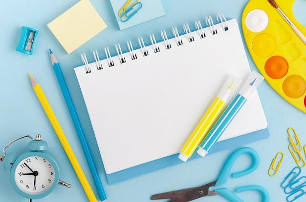 Канцелярские товары, школьные принадлежности и белый пустой записку на пастельных синем фоне. вид сверху, макет