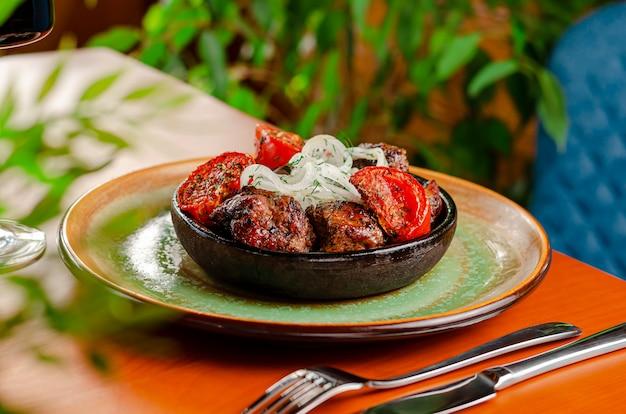 Острое барбекю на гриле на шпажках с печеными помидорами и свежим луком, подается в деревенской миске. кавказская кухня.