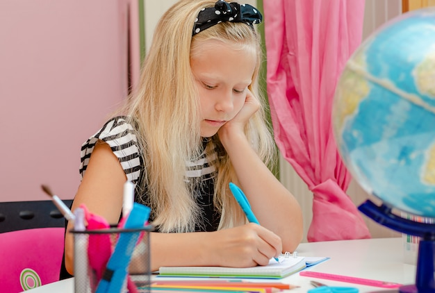 素敵な白人の学校の女の子は宿題をしながら退屈しました。教育のコンセプトです。