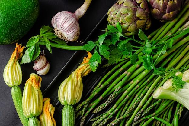 暗い背景に新鮮な緑の有機野菜。健康的な食事のコンセプト