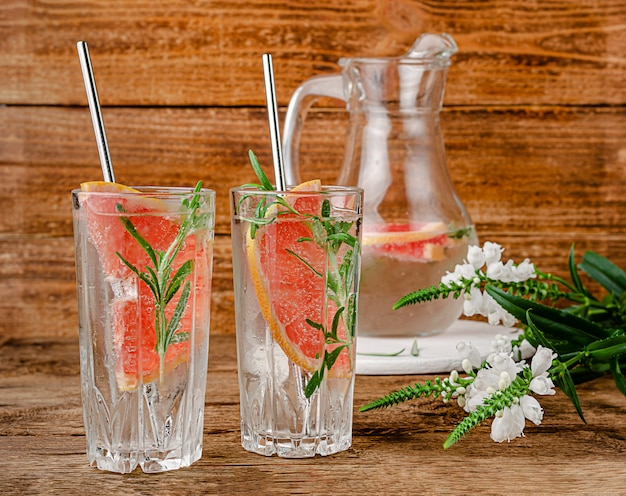 グレープフルーツは、強壮剤と木製の背景にローズマリーの水を注入しました。