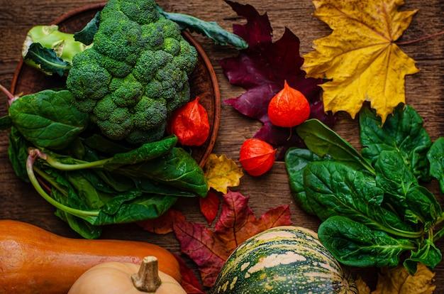 生態学的に収穫された野菜。カボチャ、ほうれん草、木製の背景にブロッコリー。平面図、フラットレイアウト。セレクティブフォーカス。