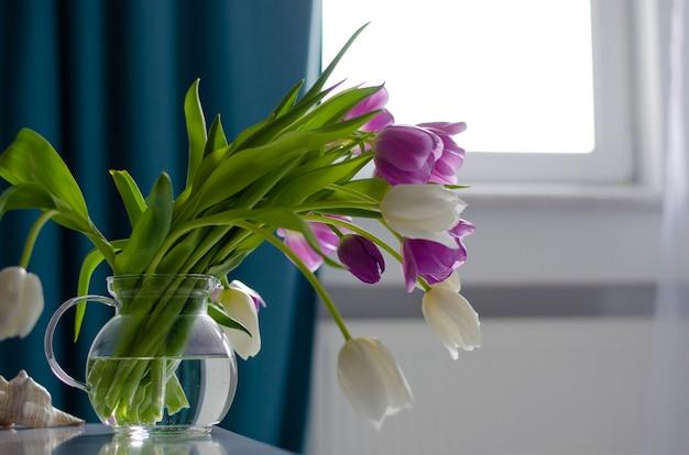Фиолетовые и белые тюльпаны на окне. копировать пространство