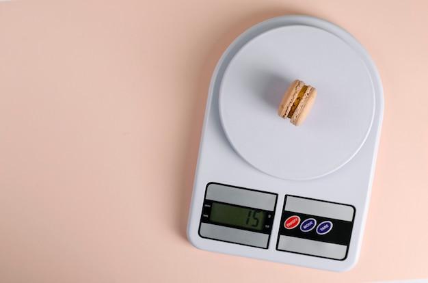Сладкое миндальное печенье на кухонные весы на бежевом