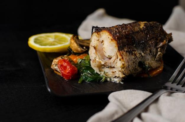 黒いプレートに焼きやオーブン焼きのメルルーサの魚。