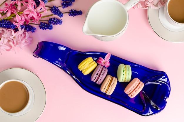 Чашка кофе с молоком, макароны, молочная банка на пастельно-розовый