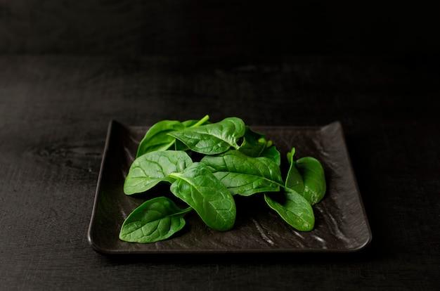 Зеленый шпинат на черной тарелке на черном фоне