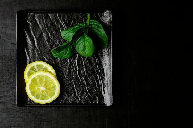 Зеленый шпинат и ломтик лимона на черной тарелке на черном фоне