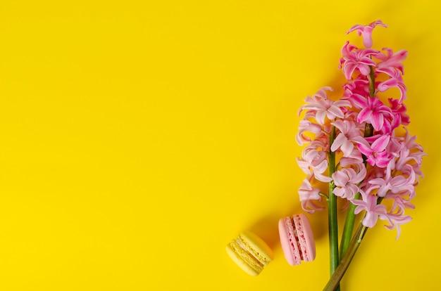 ピンクのヒヤシンスの花とマカロンまたは黄色の背景にマカロン。フラットレイアウト、トップダウン。スペースをコピーします。グリーティングカードのコンセプトです。