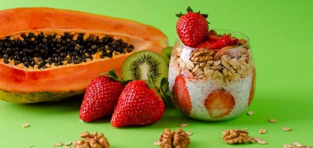 緑色の上で健康的な食事のためのオートミールとナッツと新鮮な生のトロピカルフルーツとチアプリン