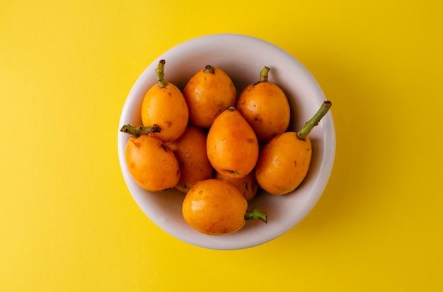 鮮やかな黄色の白いボウルにビワ果実