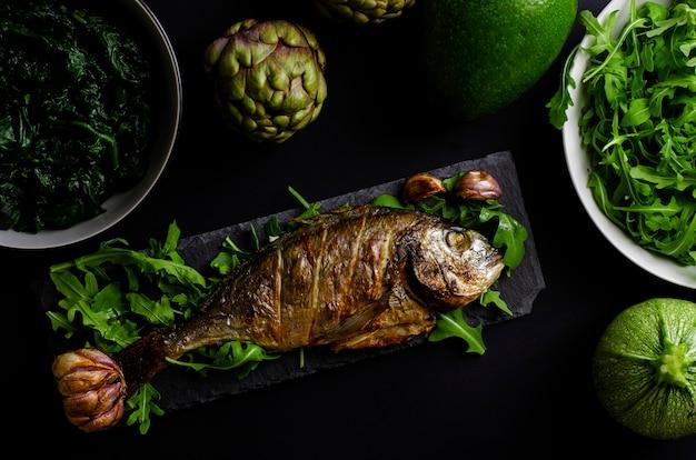 Морской лещ запеченный в духовке на черном блюдо с рукколой и зелеными овощами на черном фоне