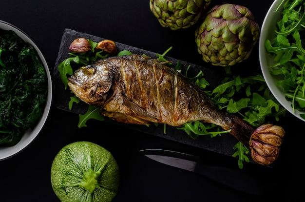 Морской лещ или рыба дорада, запеченная в духовке на черной тарелке с рукколой и зелеными овощами на черном фоне