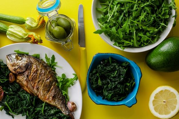 Здоровый ужин или обед с запеченной рыбой дорада или морским лещом, украшенным шпинатом и рукколой на желтом фоне