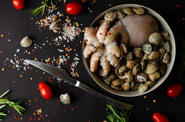 Чаша со свежим осьминогом с моллюсками и ингредиенты для приготовления пищи на черном фоне