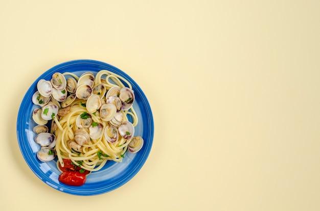 伝統的なイタリアのシーフードパスタのコンセプト。アサリまたはシェルフ、トマト、パセリのスパゲッティ。コピースペース