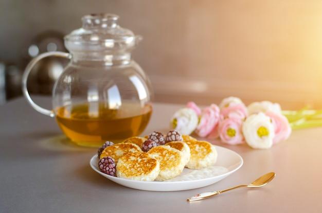 Чизкейки из творога с ежевикой на сером столе с прозрачным чайником, чайной ложкой и цветами