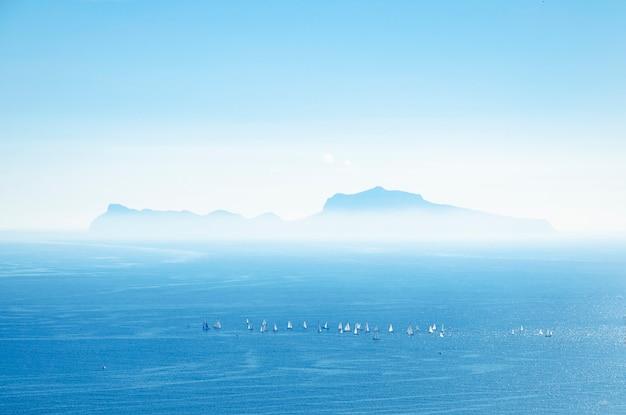 イタリアのカプリ島のシルエットのヨットのパノラマと空撮。スポーツコンセプト。