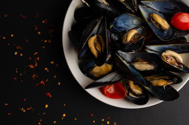 イタリアのシーフードの珍味。ムール貝のスープは、黒の背景にトマトと唐辛子とワインで蒸しました。オーバーヘッドショット、コピースペース