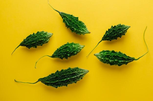Горький огурец или момордика на желтом фоне. экзотические овощи. плоская планировка