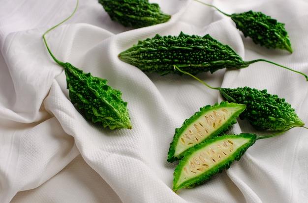 苦いキュウリまたは白い繊維の背景にモモルディカ。エキゾチックな料理。平干し