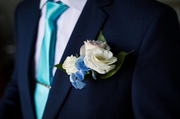 ネクタイを結ぶ青いスーツの男