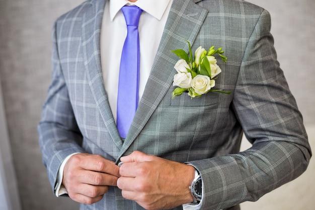 紫色のネクタイの男がチェックジャケットを締める
