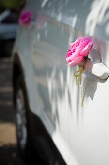 結婚式の車のドアにピンクのバラ