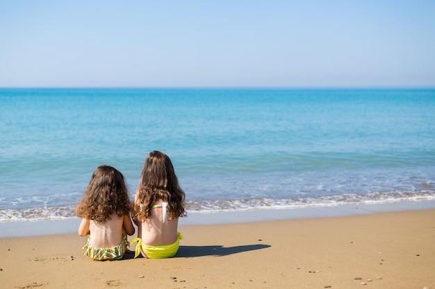 小さな女の子は砂の上に座って海を見ます。家族での休暇の概念。幸せな姉妹。コピースペース