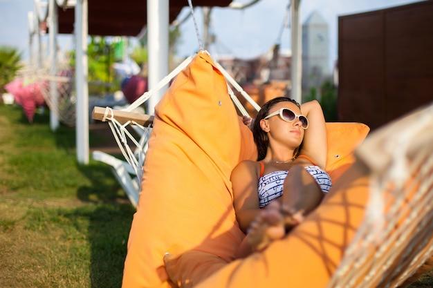 ハンモックに横たわる女。暑い晴れた日。