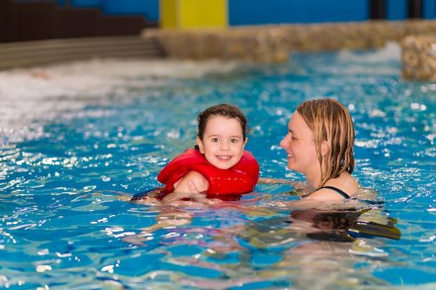 赤いベストの幸せな女の子は水公園のプールで母親と一緒に泳いでいます