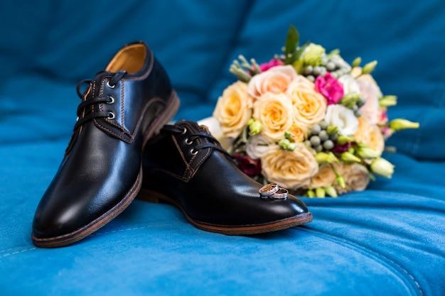 Мужская обувь обручальные кольца лежат на мужской обуви, рядом с красивым свадебным букетом