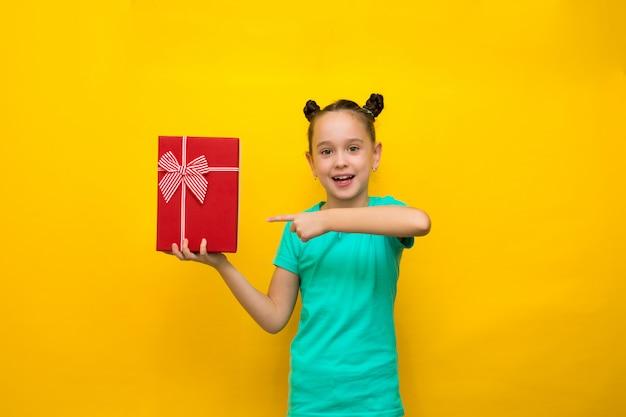 赤いギフトボックスを保持している黄色の背景に分離されて立っている幸せな女の子。