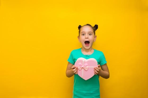 驚きに立ってピンクの買い物袋を保持している黄色の壁を越えて立っている尾を持つ幸せな女の子