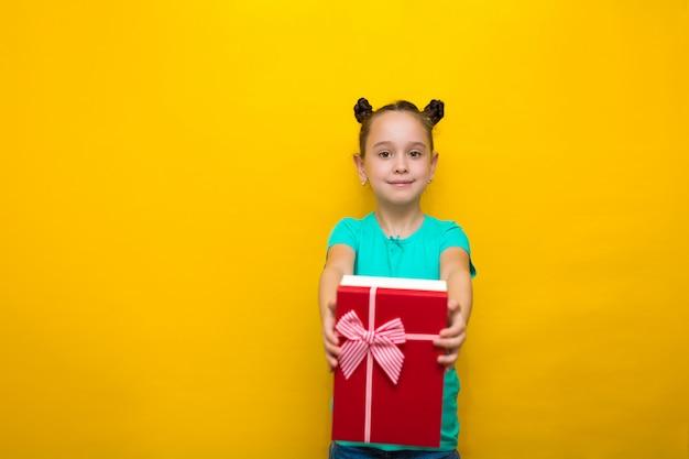 黄色の壁の上に孤立して立っている幸せな少女は、彼女の耳にそれを保持して、ボックスに驚きで耳を傾けます
