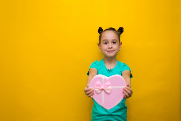 ピンクの買い物袋を保持している黄色の壁を越えて立っている尾を持つ幸せな女の子。思いやりのある笑顔