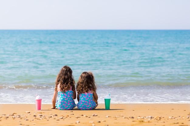 小さな女の子は砂の上に座って海を眺めます。家族での休暇の概念。幸せな姉妹。コピースペース
